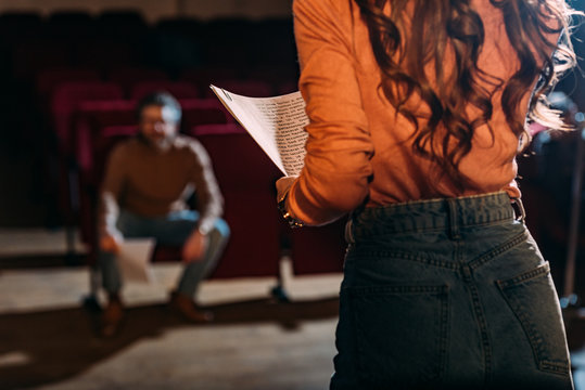 selective focus of theater director and actress with screenplay on stage