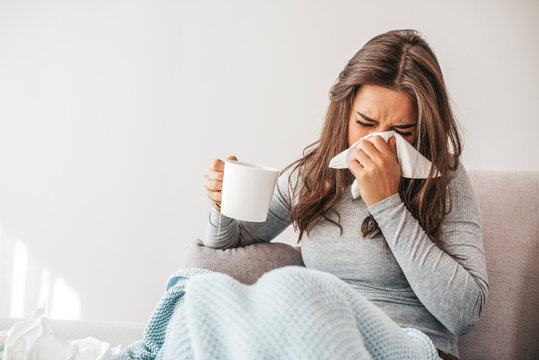 Sick woman covered with a blanket lying in bed with high fever and a flu, blowing her nose. Pills and glass of water on the table. Woman sneezing in a tissue in the living room