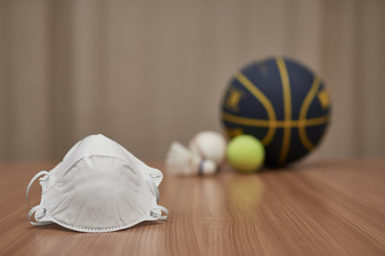 a mask in the foreground, and in the background different types of balls of different olympic sports