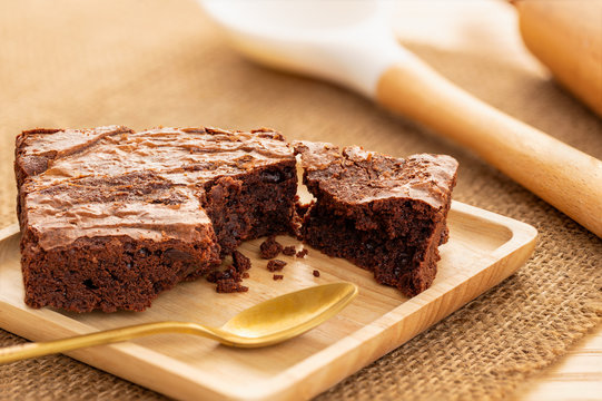 Brownies cake in a wooden plate with a golden spoon, large cooking spoon and rolling pin in the background on natural table mat..