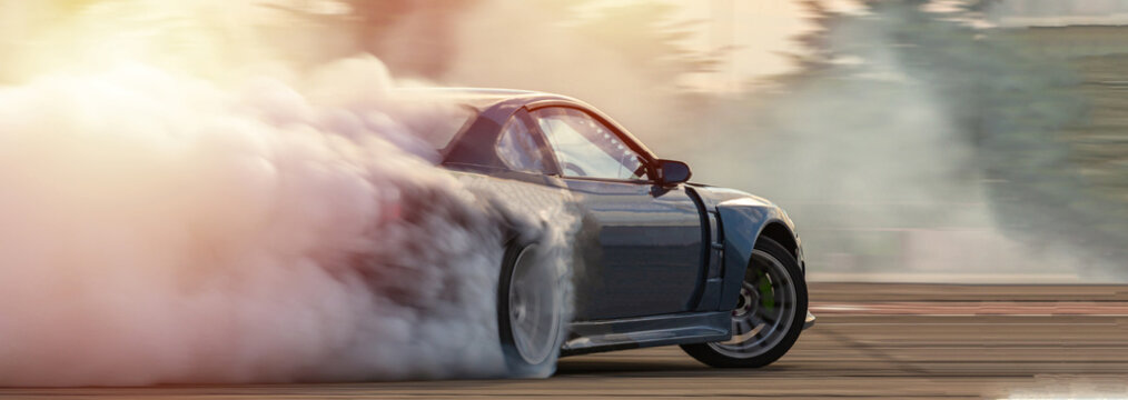 Car drifting, Blurred  image diffusion race drift car with lots of smoke from burning tires on speed track.