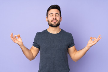 Caucasian handsome man in zen pose over isolated purple background Fototapete