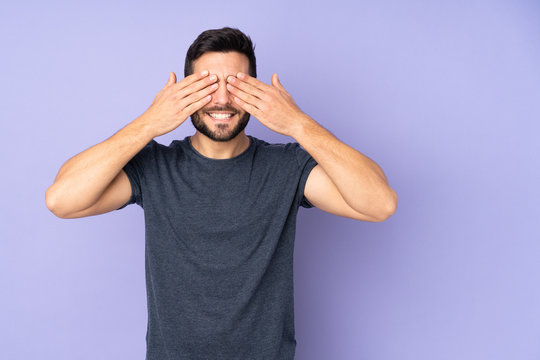 Caucasian handsome man covering eyes by hands and smiling over isolated purple background