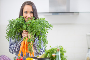 Playful young woman in her kitchen holding fresh carrot in both hands - diet vegetable and heath concept