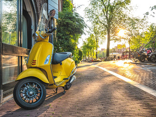 Yellow vintage scooter parked on a sidewalk. Scooter one of the most popular transport in Amsterdam