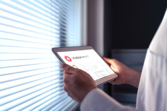 Tablet and smart technology in health care. Electronic medical record. Doctor, nurse, pharmacist or cardiologist reading EMR. Digital internet database for healthcare information. Personal report.