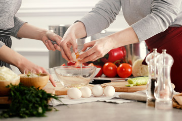 hands in the kitchen making dough on a wooden table. Free space for an advertising product