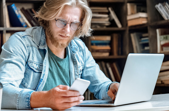 Confused perplexed man businessman student sit at office home library desk worried concerned frowning look at app modern broken stuck smartphone screen read bad news email sms message copy space.