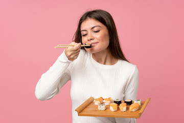 Foto op Aluminium Sushi bar Young girl with sushi over isolated pink background