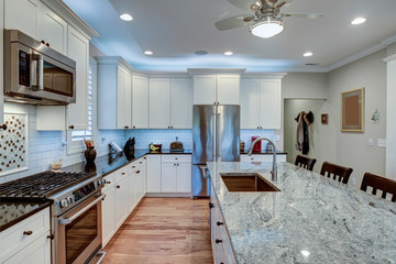 Beautiful luxury kitchen with quartz and granite countertops and white cabinets.
