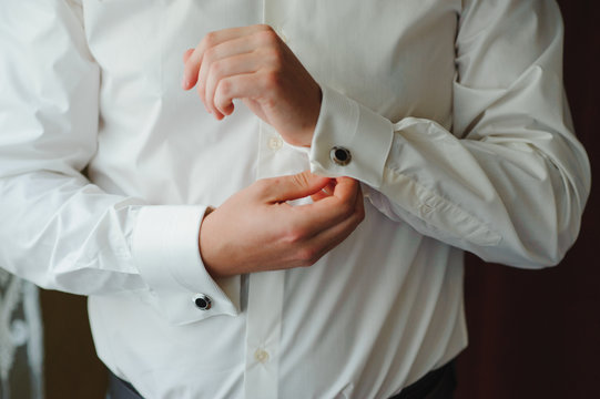 A businessman dresses a white shirt close-up, the groom prepares for the wedding ceremony. Male style. Shirts and collar cuffs