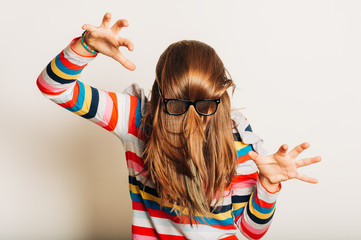 Studio portrait of young girl fooling around, hiding behind, hair, acting silly, time for haircut, hair completely covering the face with glasses over