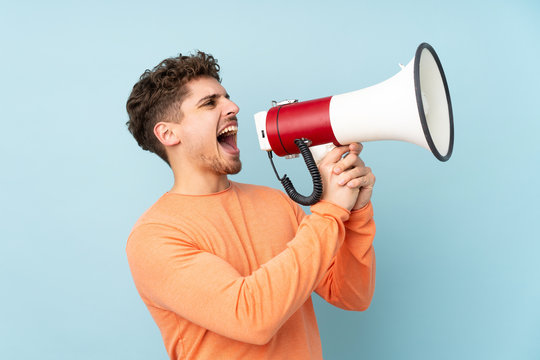 Caucasian man isolated on blue background shouting through a megaphone