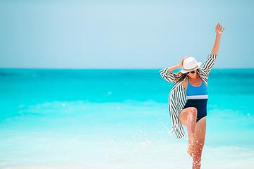 Foto auf Leinwand Sansibar Young happy woman in swimsuit on white beach