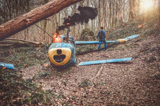 petit avion en flamme  tombé dans un bois avec un survivant