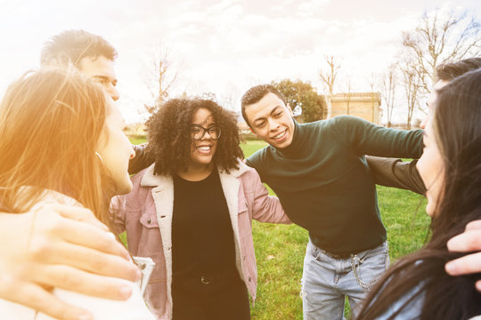 Group of teenagers of different cultures hugging each other at the park - Teamwork of young people forming a semicircle - Six men and women having fun together