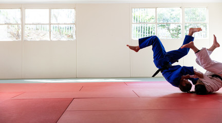 Judokas practicing judo during a sparring in a gym