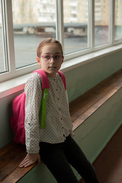 Girl 9 years old with a school backpack on her back. Portrait of a schoolgirl 9 years old. 4th grade school.