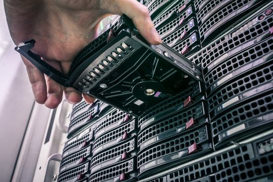 Replacing a module in a powerful server hardware. Cloud storage technology concept. Hosting platform of the Internet provider. Connect a new hard drive to a stack of computer servers
