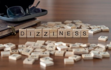 dizziness concept represented by wooden letter tiles on a wooden table with glasses and a book