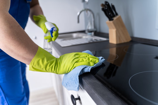 Male Janitor Cleaning Kitchen Counter