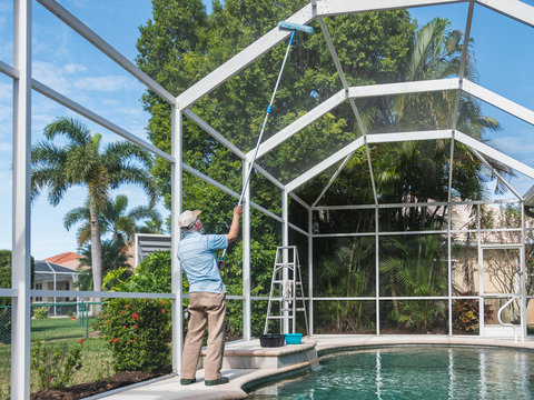 Handyman cleaning outdoor pool cage enclosure with pole brush. Screened swimming pool lanai maintenance and screen repair.