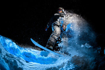 Male snowboarder doing stunts on blue light background