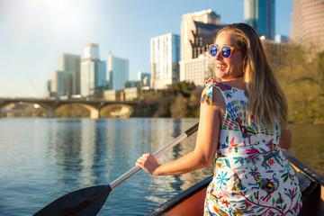 Fototapeta A beautiful traveller enjoying a tourist attraction adventure, kayaking the river near an urban city skyline in the summer obraz