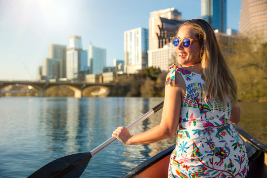 A beautiful traveller enjoying a tourist attraction adventure, kayaking the river near an urban city skyline in the summer