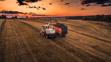 Foto auf Leinwand Rotglühen Harvesting equipment in a sunset meadow, with a variety of furrows from work.