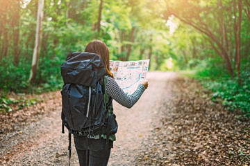 Fototapeta Traveling Happy Asian woman with backpack walking on path the tropical forest looking at the camera and map in green rainforests. Summer holiday and vacation trip , Survival travel, lifestyle concept obraz