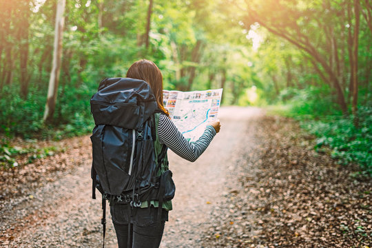 Traveling Happy Asian woman with backpack walking on path the tropical forest looking at the camera and map in green rainforests. Summer holiday and vacation trip , Survival travel, lifestyle concept