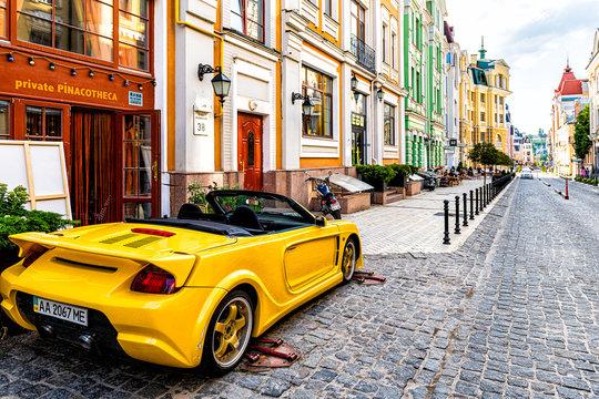 Kyiv, Ukraine - August 13, 2018: Old historic colorful street buildings of Kiev city in Podil vozdvizhenka neighborhood multicolored and yellow car