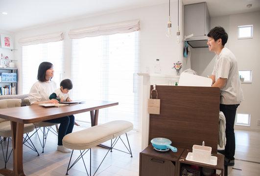家事をする父親と子供に本の読み聞かせをする母親
