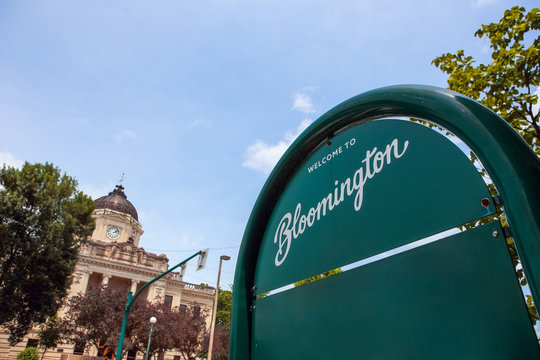 Welcome to Bloomington Indiana sign with downtown courthouse in the background