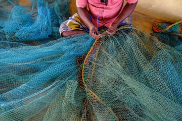 A man repairing nets in the fishing district of Jaffna in Sri Lanka.
