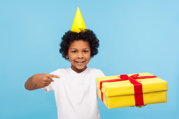 Look at my birthday present! Cheerful adorable little boy with party cone on head pointing at gift box and smiling at camera, happy child satisfied with holiday surprise. studio shot blue background