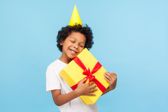 Amusing happy pleased little boy with party cone on head embracing gift box and closing eyes in pleasure, child enjoying long-awaited birthday present, dreams come true. studio shot blue background