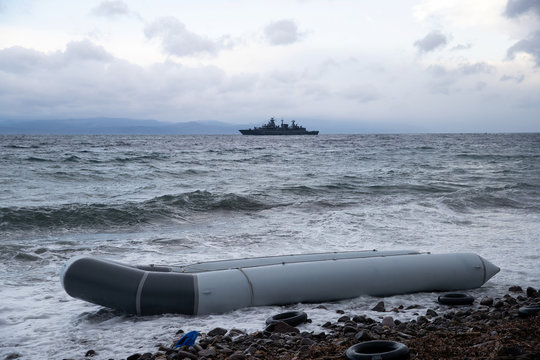 A dinghy used by migrants from sub-saharan African countries to cross part of the Aegean Sea from Turkey in seen on a beach near the village of Skala Sikamias, with the the German frigate Mecklenburg-Vorpommern seen on the background, on the island of Lesb
