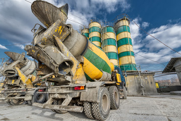 Concrete mixing plant. Two concrete trucks stand near the cement storage towers.