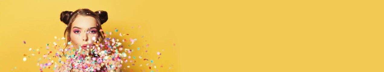Beautiful woman blowing colorful confetti on yellow banner background