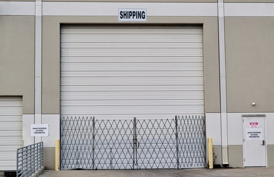 Single closed loading dock door with security gate and shipping sign above it. Warehouse distribution and freight transportation concept.
