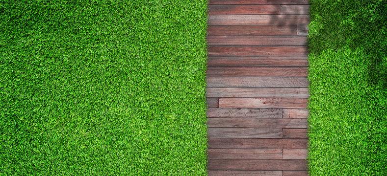 Outdoor gardening design of Top view green artificial grass with wooden footpath in garden.