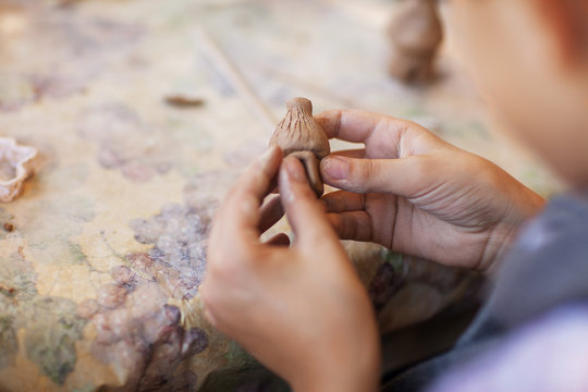children make clay figures by pottery