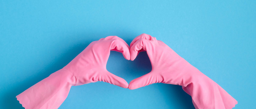 Heart shaped hands in pink rubber gloves over blue background. House cleaning service and housekeeping concept