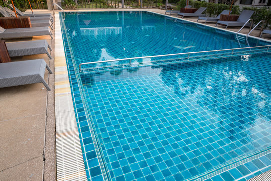 Swimming Pool.swimming pool bottom caustics ripple and flow with waves background.Swimming pool of luxury hotel.
