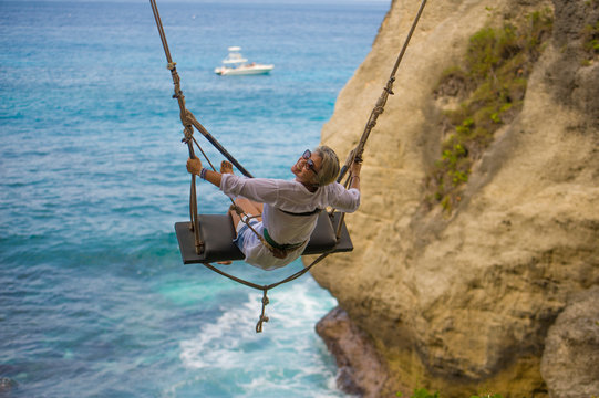 mature attractive and happy woman on with grey hair enjoying amazing sea view from swing feeling young and free swinging carefree having beautiful retirement