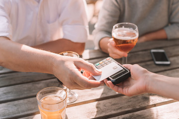 Close-up of male hand paying at restaurant with credit card - lifestyle picture of people relaxing at brewery and paying with plastic card at the table