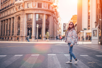 Smiling girl walking down the street, crossing the road at a pedestrian crossing. Sunny spring day, image with copy space