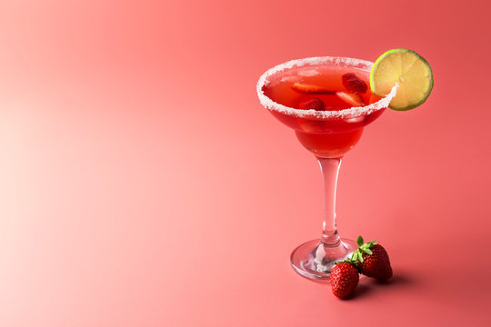 Strawberry margarita alcoholic cocktail with tequila, liqueur, berries, lime juice, sugar and ice, pink background, copy space